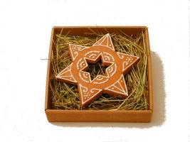 Piernikowa gwiazda z dziurką w kształcie gwiazdki, w pudełku na sianku.