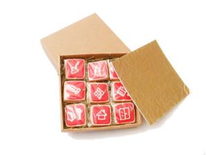 dziewięć kwadratowych pierniczków z czerwoną polewą i białymi ikonami produktów w pudełku kwadratowym, prócz tego wieczko pudełka i złota kołderka amortyzująca