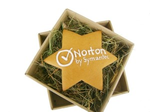 Piernik z logotypem w kształcie gwiazdy z lukrowanym: Norton by Symantec, w pudełku na sianku.